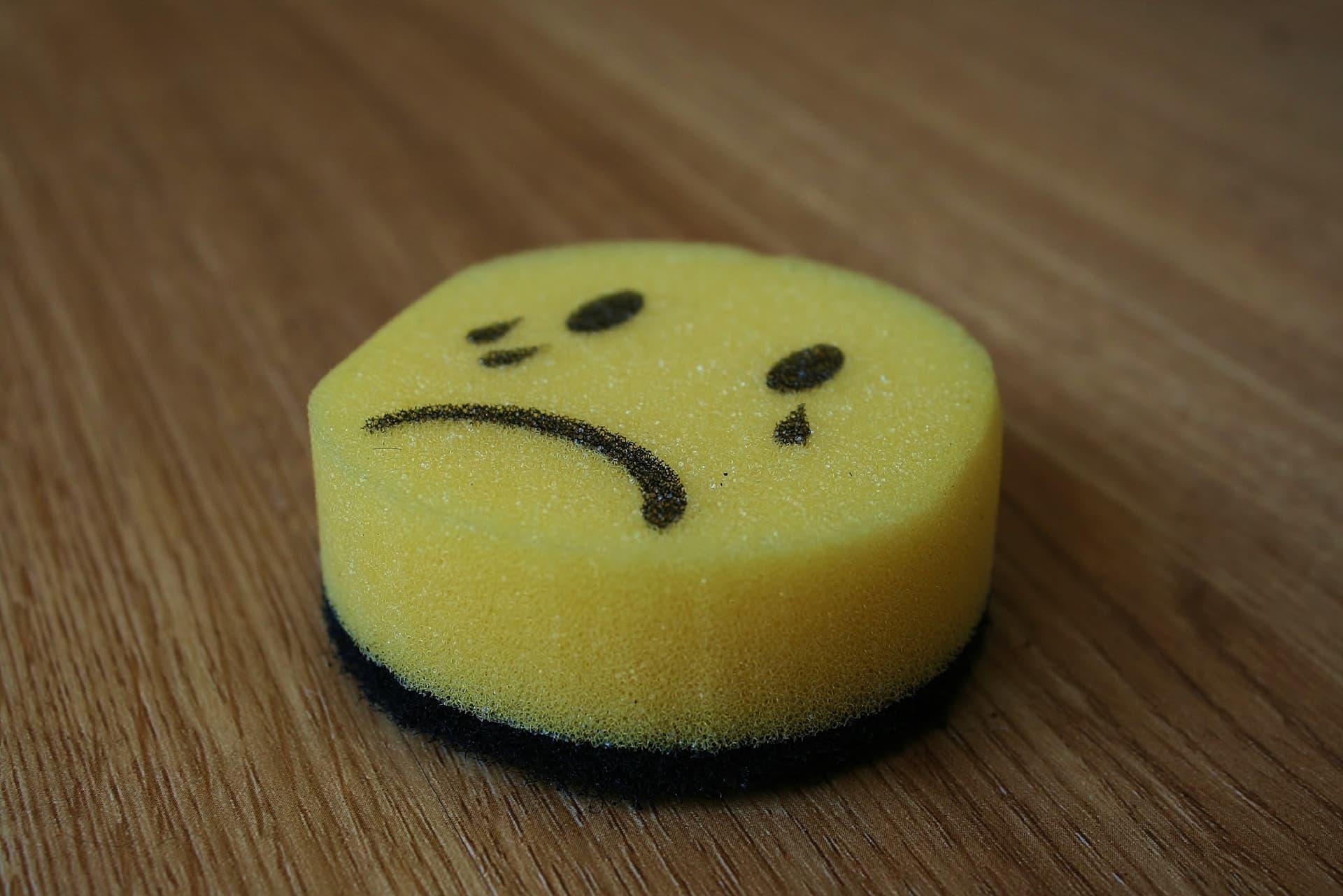 Circular sponge with the crying emoji drawn on it